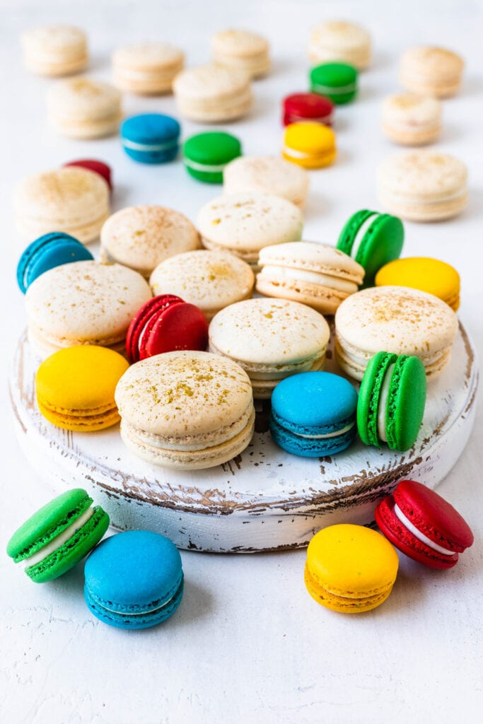 white macarons with gold splatter on top surrounded by blue, yellow, red, green macarons.