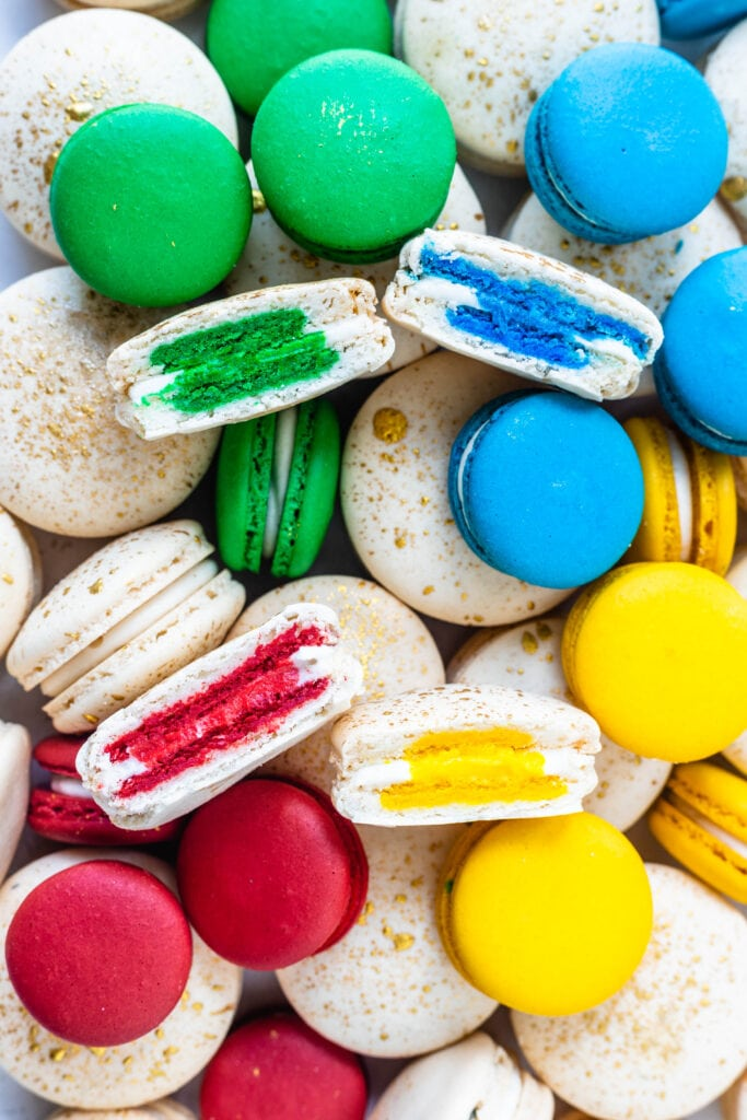4 macarons sliced in half, each has a different color in the center, red, yellow, blue and green, and on the background there are several white macarons, as well as blue, yellow, red, and green ones.