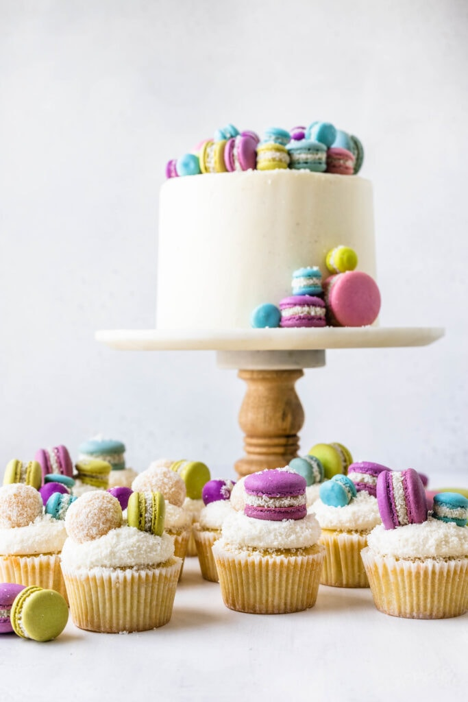 cake topped with macarons and coconut cupcakes around topped with colorful macarons.