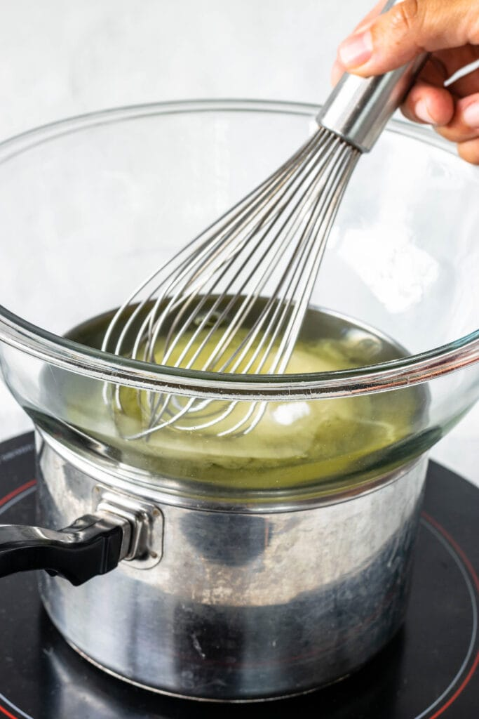 whisking egg whites and sugar over a double boiler.