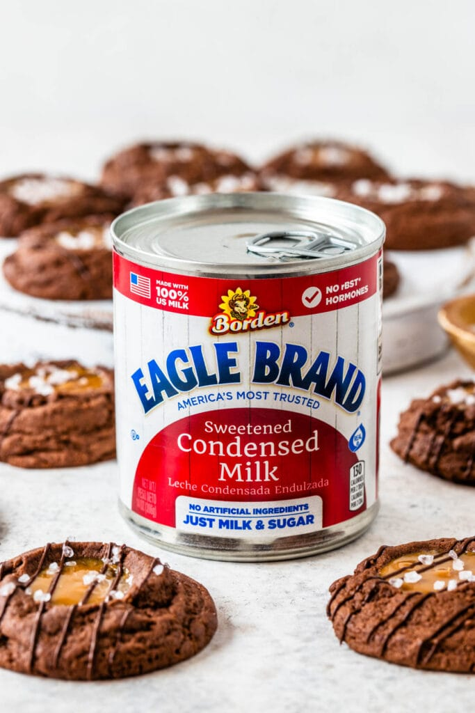 chocolate cookies with a dulce de leche center and salt sprinkled on top and a drizzle of chocolate with a can of condensed milk.