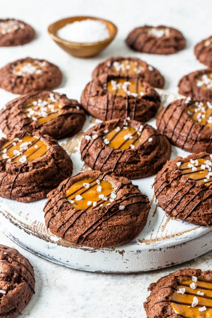 chocolate cookies with a dulce de leche center and salt sprinkled on top and a drizzle of chocolate.